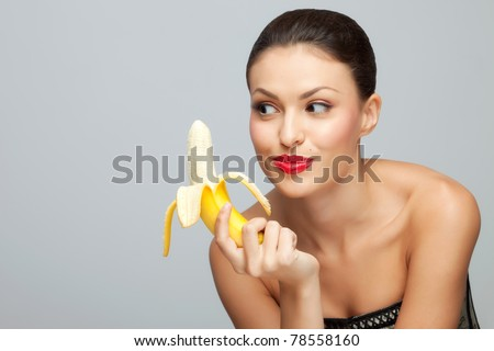 Wanna some? A starving sexy woman holding a half-peeled banana in her hand.
