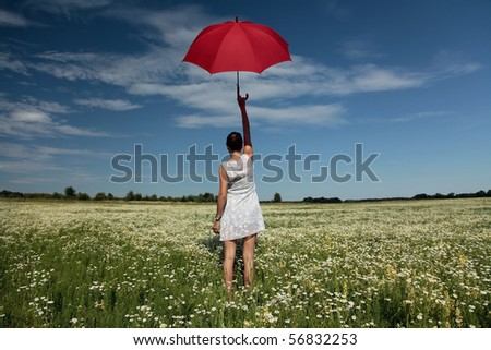 Want to fly. Woman with red umbrella above the head standing on meadow