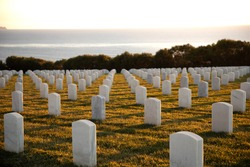 War cemetery with rows of white marble graves on green grass at sunset with ocean view. Marine veteran's cemetery.