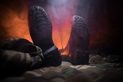 War concept. Old military shoe in a dark toned foggy background. Boots on soldier who KIA (Killed in action). Selective focus