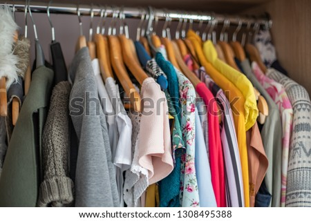 Wardrobe closet full of colorfull clothes in dressing-room. #1308495388