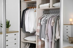 Wardrobe closet with different stylish clothes in room, closeup