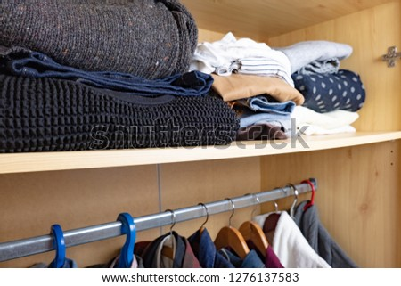 Wardrobe shelf with abundance of clothes. Consumerism concept: organised and layered personal things in a wooden closet