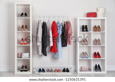 Wardrobe shelves with different stylish shoes and clothes indoors. Idea for interior design #1250631391