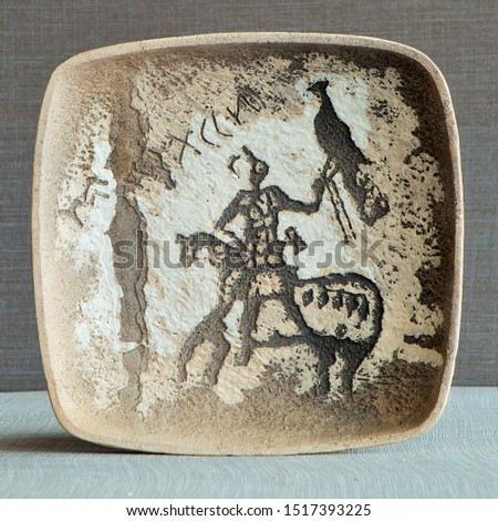 Ware from ceramics. Pictograms of nomadic peoples are displayed on the dishes. #1517393225
