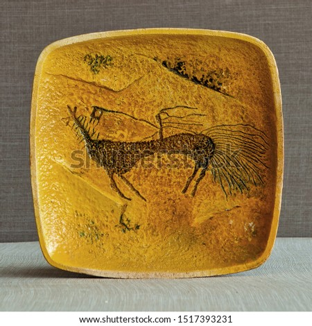 Ware from ceramics. Pictograms of nomadic peoples are displayed on the dishes. #1517393231