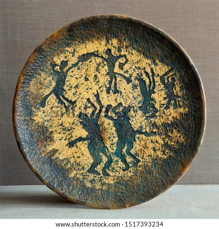 Ware from ceramics. Pictograms of nomadic peoples are displayed on the dishes. #1517393234