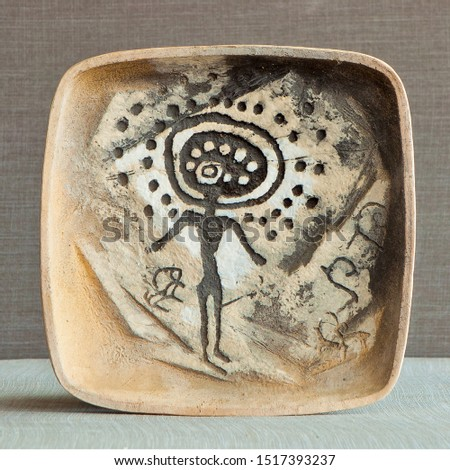 Ware from ceramics. Pictograms of nomadic peoples are displayed on the dishes. #1517393237