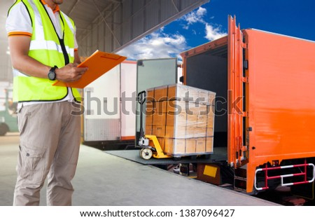 warehouse and logistics, freight transportation. courier shipment transportation. worker man in uniform is checking load the shipment transport by truck.