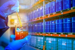 Warehouse chemical products. Concept - crude oil in blue barrels. Oil is prepared for export. Laboratory assistant took a sample for verification. Checking oil products for quality. Barrel shelving