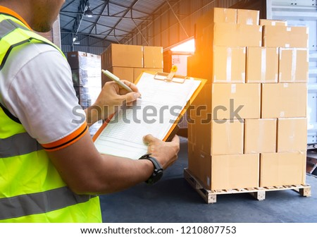 Warehouse courier shipment transport. Stack cardboard boxes on pallet. Warehouse worker writing on clipboard inspecting checklist cargo shipment products for load into a truck.