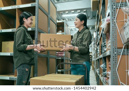 Warehouse coworker women passing cardboard box in large storehouse. young girl employee pushing cart walking in stockroom and stopping by colleague. elegant lady manager give parcels to staff. #1454402942