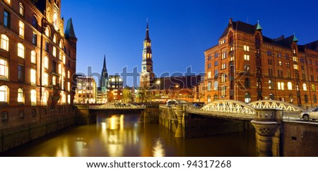 Warehouse district ( Speicherstadt ) of Hamburg at night with view towards the city center including the St. Catherine's Church and St. Nikolai