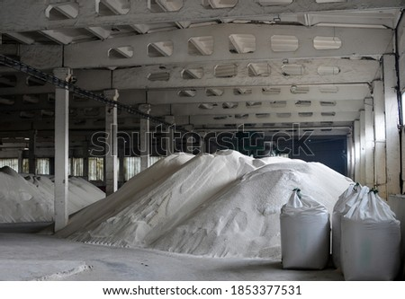 Warehouse for storing white granulated phosphate fertilizers. Packing in pile jumbo-bags. Photo stock ©