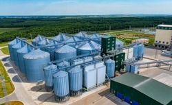 Warehouse granary aluminum containers. Grain silo and parking place. Steel grain elevators. Agriculture Industry. High angle view