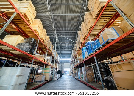 Warehouse industrial and logistics companies. Commercial warehouse. Boxes and crates stocked on the shelves of three storey. Toning the image.
