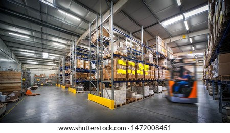 warehouse interior wit blurred forklift and worker in logistic center
