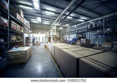 warehouse interior with paper boxes and worker with forklift in blue vintage color tone #550051702