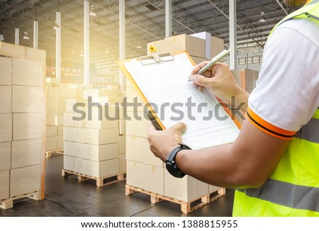 Warehouse inventory and management.  courier shipment transportation. stack of cardboard boxes on wooden pallet. warehouse worker is writing on clipboard is checking cargo in distribution warehouse.
