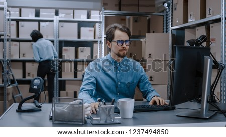 Warehouse Inventory Manager Works on Computer while Sitting at His Desk, In Background, Female Worker Check Shelf for a Delivery Package. Shelves are Full of Cardboard Box Packages Ready For Shipping.