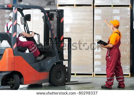 warehouse laborer team at unloading works with forklift loader