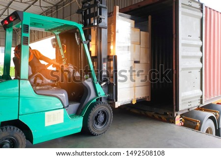 warehouse logistics and transportation, forklift driver loading cargo pallet shipment into a truck container.
