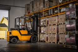 Warehouse man worker with forklift. Warehouse worker driver in loading by forklift stack loader