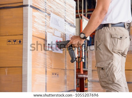 Warehouse manager holding barcode scanner with scanning on the shipment pallet for deliver to customer.