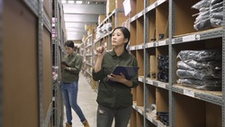 warehouse manager woman holding clipboard and pen in hands. two colleague girls staffs standing in storage full of boxes and counting material in stockroom. female employees work in storehouse