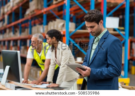 Warehouse managers and worker working together in warehouse office #508535986