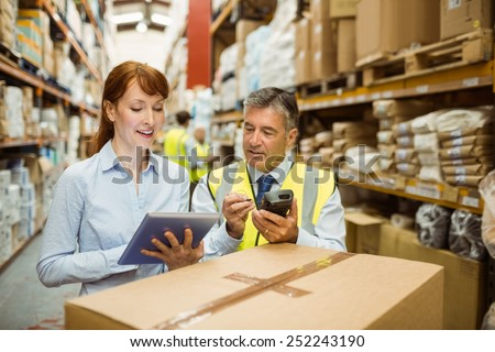 Warehouse managers looking at tablet pc in a large warehouse #252243190