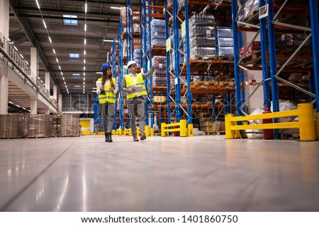 Warehouse managers walking in a large storage department controlling distribution to the market.