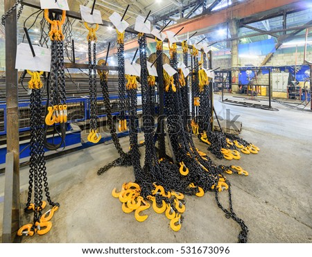 Warehouse of finished products of the enterprise for the production of handling removable devices. Rack with new cargo chain slings. #531673096
