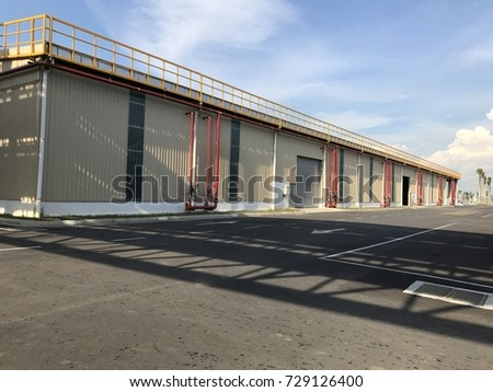 Warehouse outdoor during the sunny day with cloudy blue sky.  #729126400