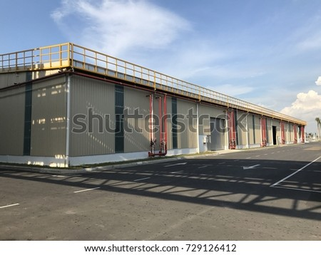 Warehouse outdoor during the sunny day with cloudy blue sky.  #729126412