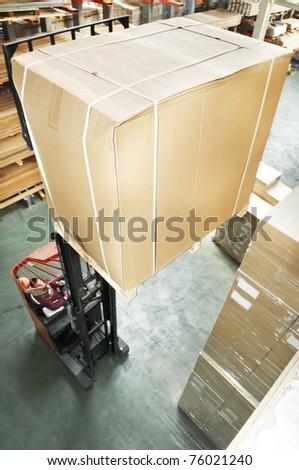 warehouse stacker forklift lifting large cardboard box