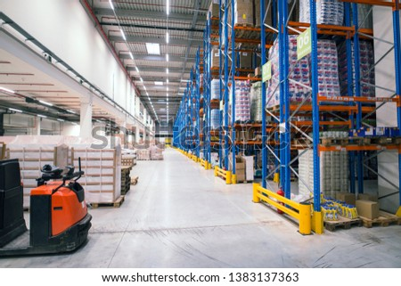 Warehouse storage facility interior. Large distribution center with shelves full of palette boxes and forklift machine. #1383137363