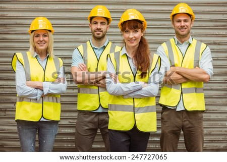 Warehouse team with arms crossed wearing hard hat in a large warehouse #247727065