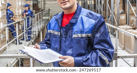 warehouse three workers- one man and two woman in a special blue uniform is recording and accounting of contents in cardboard boxes in stock No faces idea account statistics cargo arrival No face