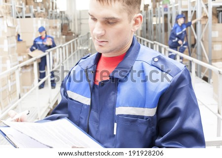 warehouse three workers one man and two woman in a special blue uniform is recording and accounting of contents in cardboard boxes in stock No faces idea account statistics rediscount cargo arrival