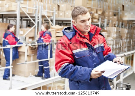 warehouse three workers - one man and two woman in a special uniform is recording and accounting of the contents in cardboard boxes in stock