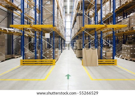 Warehouse with racks and shelves, filled with cardboard boxes, wrapped in foil on wooden pallets