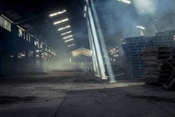 Warehouse with shafts of light pouring through roof