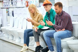 warehouse worker and customers sit on toilet bowl, use smartphones, shopping concept, side view
