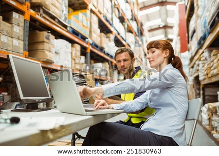 Warehouse worker and manager looking at laptop in a large warehouse #251830963
