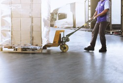 Warehouse worker dragging hand pallet truck or manual forklift with the shipment pallet unloading into a truck.