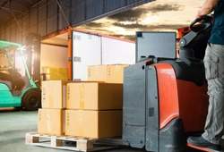 Warehouse worker driving forklift pallet jack unloading pallet goods, package boxes, forklift loading shipment goods into a truck, road freight, warehouse industry delivery logistics and transport.