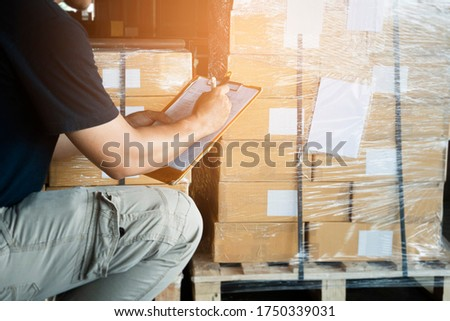 Warehouse worker holding clipboard writing on checklist for delivering shipment goods. Package boxes, Cargo shipment export, Industry warehouse shipping logistics and transport.