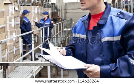 warehouse worker in a special uniform is recording and accounting of the contents in cardboard boxes in stock