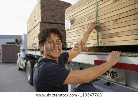 Warehouse worker loading wooden planks on truck carrier